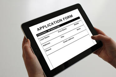 Canva - Hands Holding Tablet With Application Form